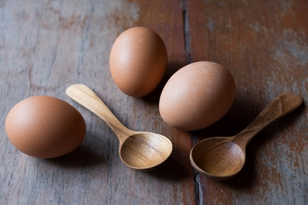 Eggs and wooden spoons on wood backgrounds Stock Photo