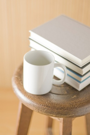Wooden wall with old chair and books and cup photo