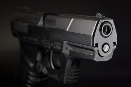Close Up of pistol on black background photo