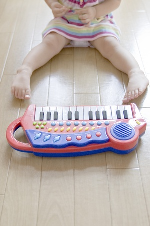 A little girl playing on a keyboard instrument. photo