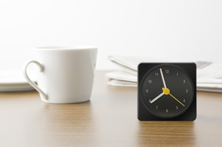 Desk clock and cup and newspaper photo