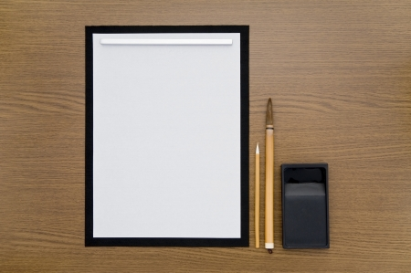inkstone: Blank paper and calligraphy set on wooden table
