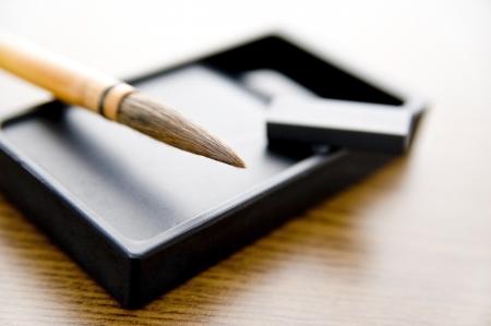 茶色の木製のテーブルの上にブラシとインク石