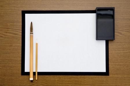 茶色の木製の背景にブラシとインク石を書く 写真素材