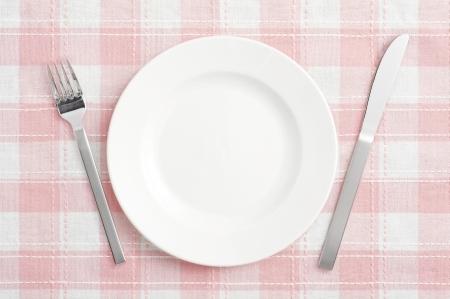 Blanc assiette vide avec une fourchette et un couteau sur le tapis rose ch�que