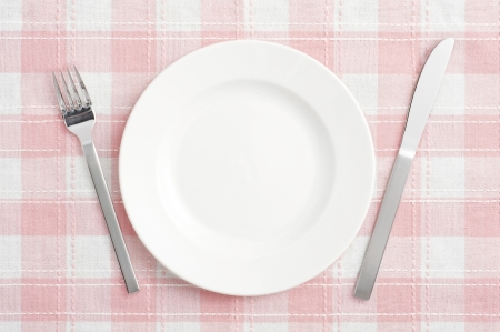 kitchen table: White empty plate with fork and knife on pink check mat  Stock Photo
