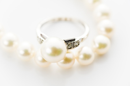 Pearl necklace and ring on white back ground photo