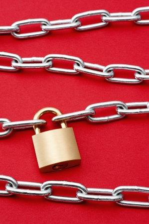 Padlock with chain on red background  Stock Photo - 16277491
