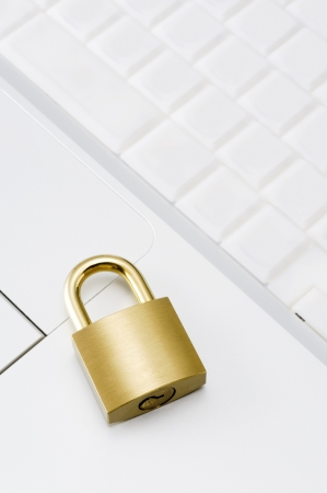 Personal computer with key board and gold padlock, close-up shoot  photo