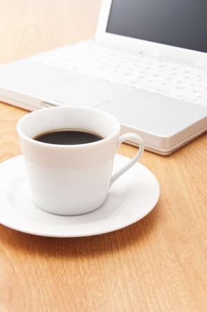 Notebook PC and coffee on wooden table photo