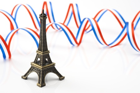 french model: eiffel tower figurines with ribbon on white background