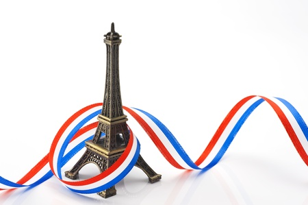 eiffel tower figurines with ribbon on white background photo