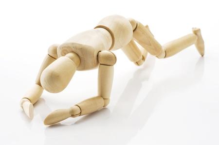 saddened: Wooden doll fell down on white background