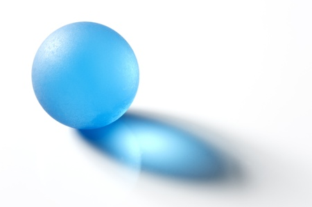 Blue glass marble on white background, close-up