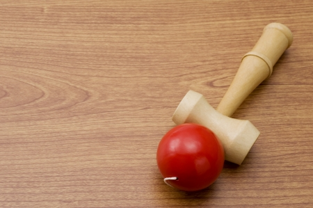 Classic wooden bilboquet with red ball on wooden table