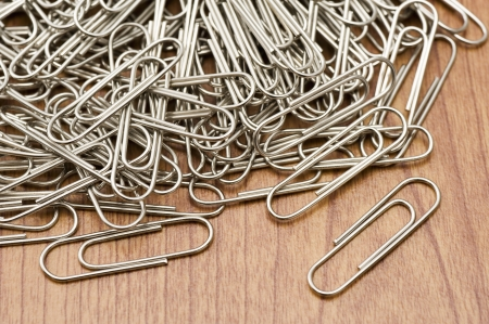 A lot of silver paper clip on wooden table Stock Photo - 16330636