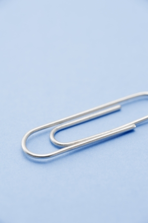 Silver paper clip on blue background, close-up  Stock Photo - 16326390