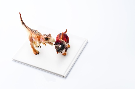 Dinosaur toy and book on white background  Stock Photo - 16339282