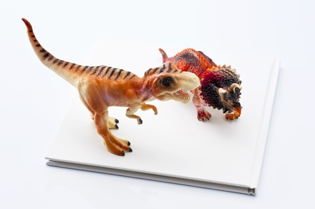 Dinosaur toy and book on white background  photo