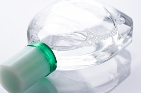 Transparent bottle of eye drops on white background