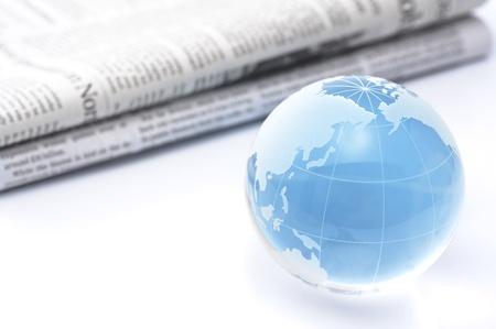 ガラス グローブと白い背景の上の新聞
