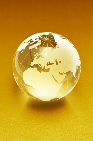 Clear glass globe on gold color background  photo