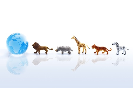 Animal toys and clear glass globe on white background  photo