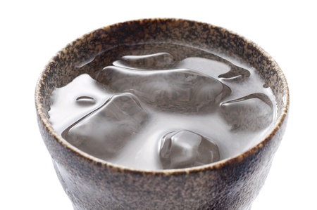 distilled: Distilled spirit into the pottery cup on white background  Stock Photo