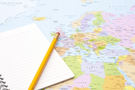 map pencil: blank notebook and pencil on world map background