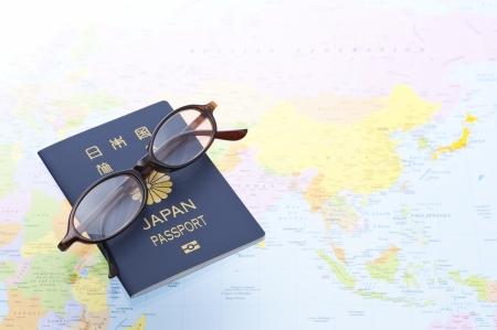 日本のパスポートと背景を世界地図上の眼鏡