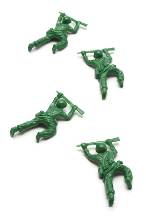 green military miniature: miniture toy soldiers advancing creeping on white background