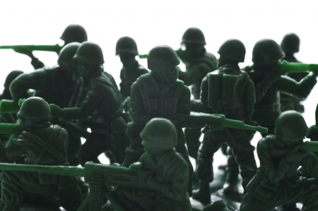 green plastic soldiers: miniture toy soldiers with guns on white background