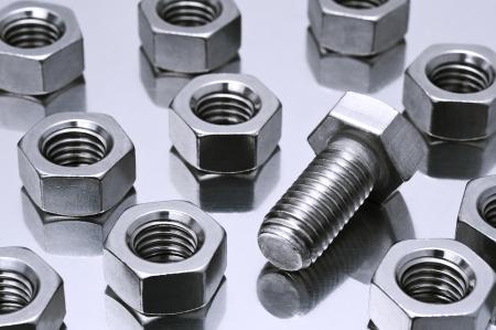 tuercas y tornillos: pernos y tuercas de metal sobre fondo de plata Foto de archivo