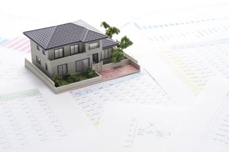 ein Miniatur-Haus und Business-Dokument
