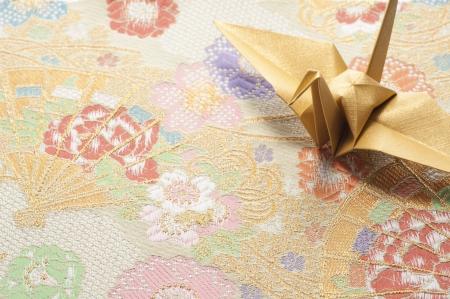 origami crane on japanese textile background photo