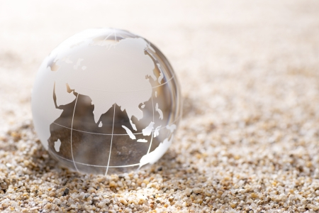 Transparent glass globe on sand background photo