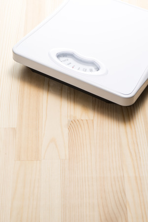 Analog weight scale on wooden floor photo