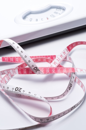 Close-up of a tape measure and Bathroom scale photo