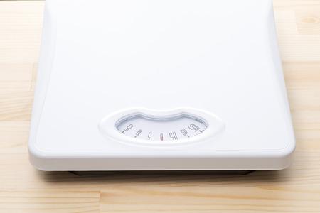 Bathroom scale on a wooden floor photo