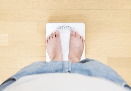 weighing scale:  Foot of man standing on bathroom scale Stock Photo