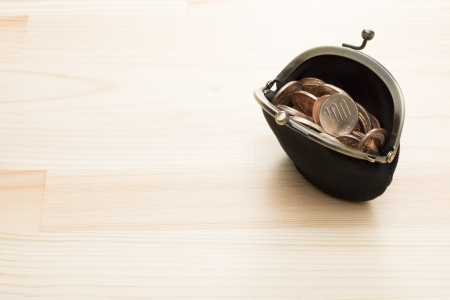 retro: black purse with coins on wooden background