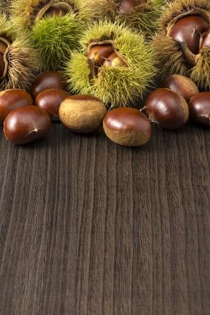 husk: muchas casta�as con c�scara en mesa de madera oscura