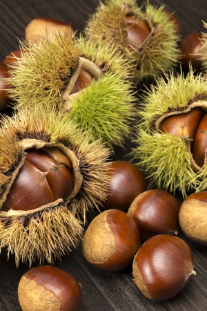 many chestnuts with husk on dark wooden table