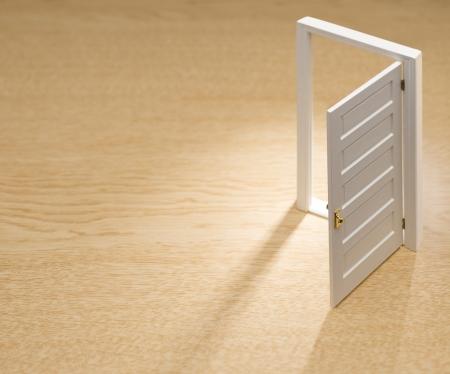 Opened door on wooden background photo