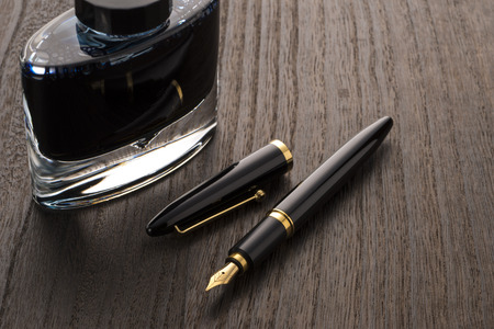 fountain pen and ink bottle on table 写真素材