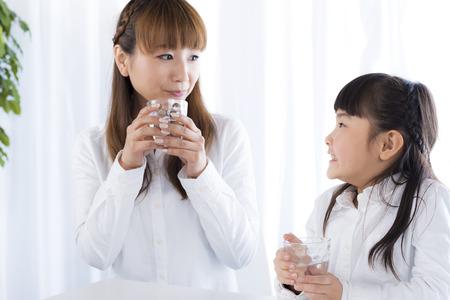 母と娘がある水を飲む 写真素材