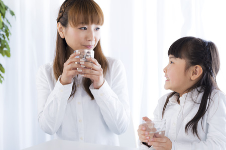 children water: mother and daughter have a drink of water Stock Photo