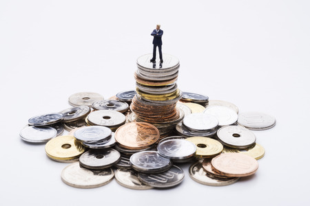 coin stack: The doll business man on top of the stacked coins Stock Photo