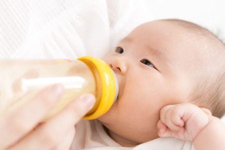 Baby drinking milk in a baby bottle