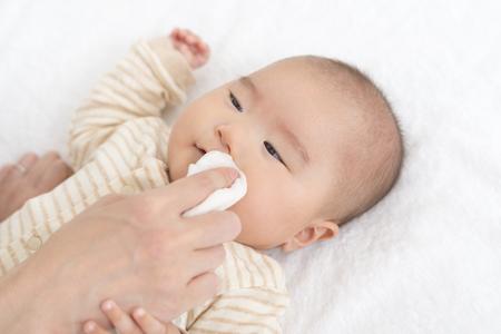 ガーゼで赤ちゃんの顔を拭く